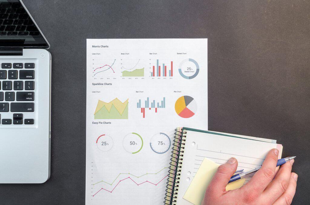 A imagem é uma fotografia em formato retangular. A imagem mostra a vista superior de uma mesa cinza. No lado esquerdo da imagem está um notebook de tela preta sobre a mesa. Ao lado do notebook, há uma folha de papel sulfite branco. Na folha há desenhos de gráficos. No canto inferior esquerdo, há um caderno pautado. Sob o caderno, há uma mão segurando uma caneta azul.