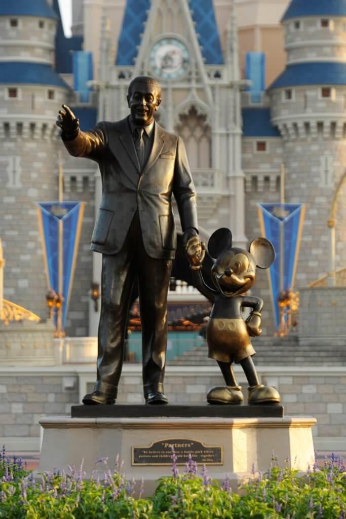 estatua do Walt Disney de mãos dadas com o Mickey, em frente ao castelo da Cinderela em um dos parques temáticos.